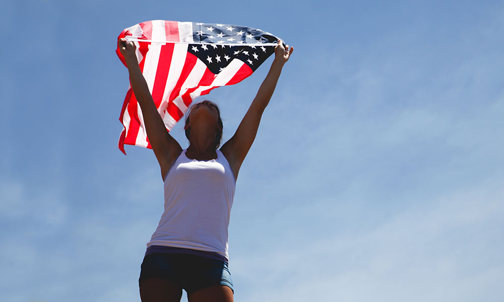Runner Holding American Flag above her head against a clear blue sky